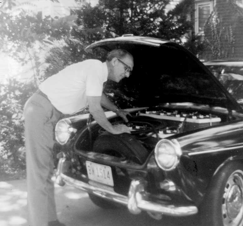 Bud Wheeler inspecting the front battery bank in his electric car.